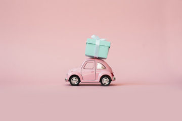 pink-toy-retro-model-car-delivering-gift-box-pink-background_69064-231